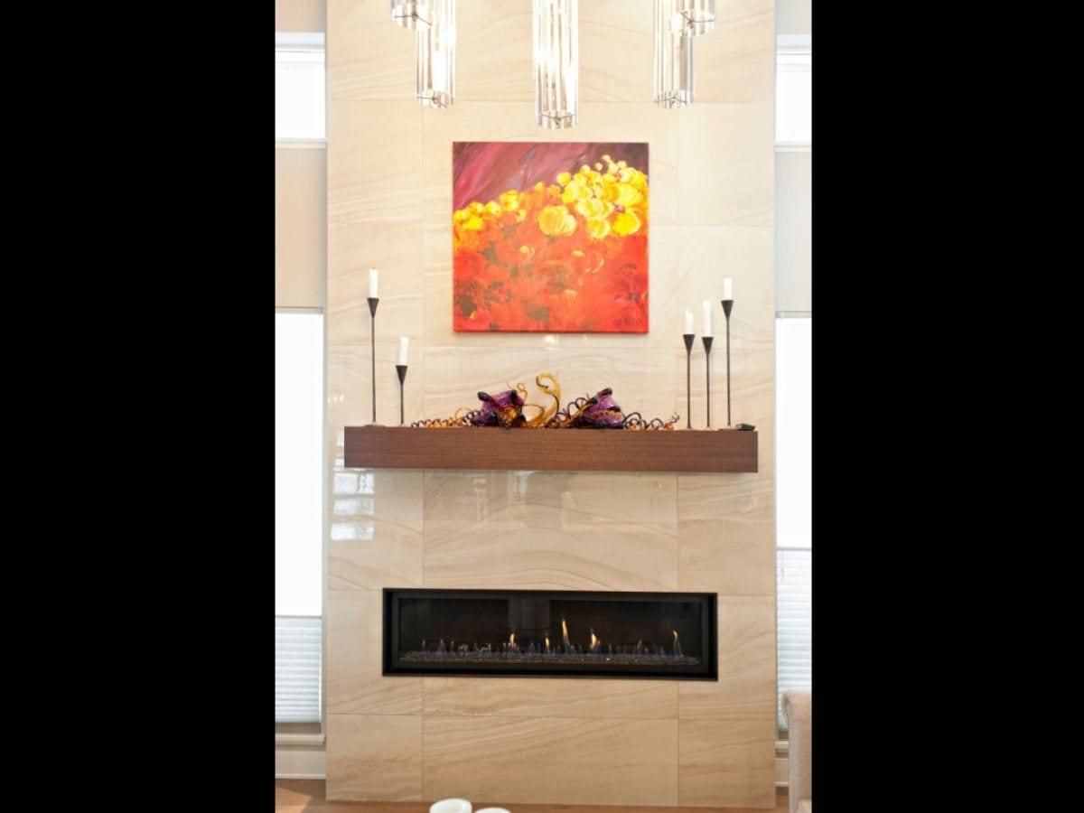 Piece of brightly colored art hung above a fireplace