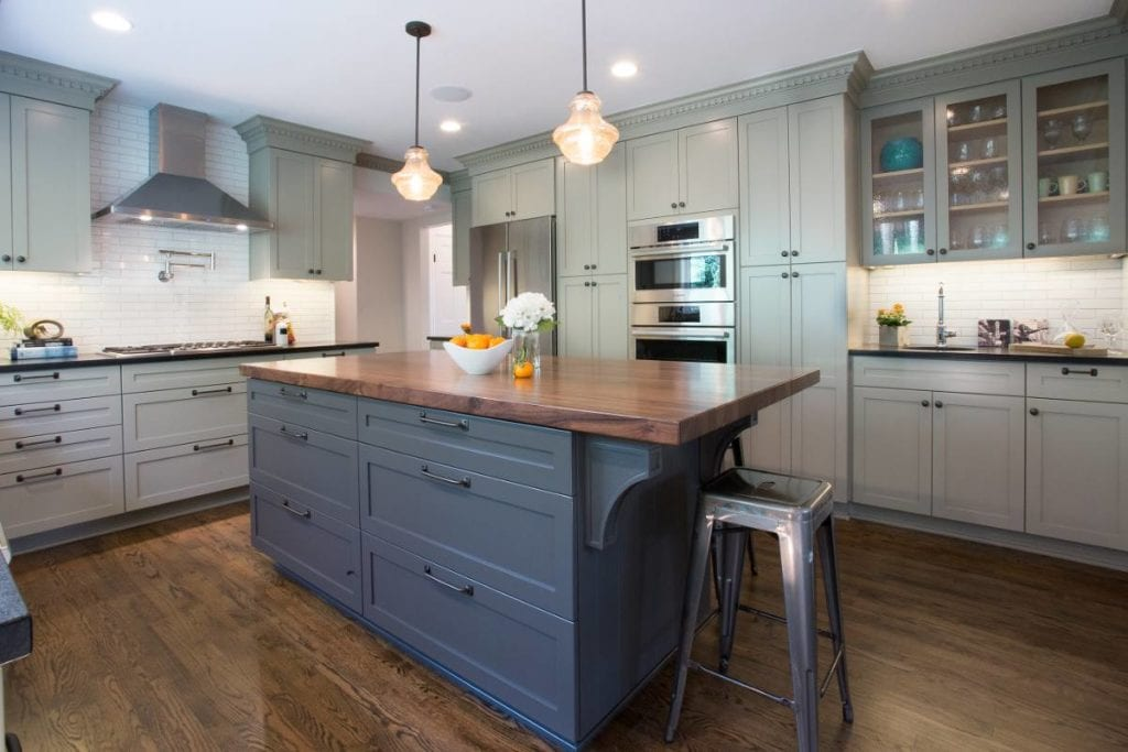 Updated kitchen with mixed cabinets, variety of colors, and interesting lighting