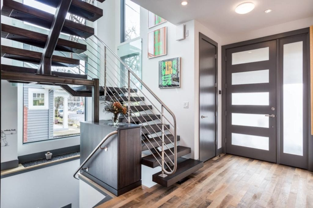 Interior of a modern home with floating staircase, updated doors, hardwood floors, and several windows